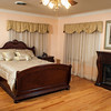 Jim and Marla Halbrook's master bedroom is done in dark furniture with a large electric fireplace.