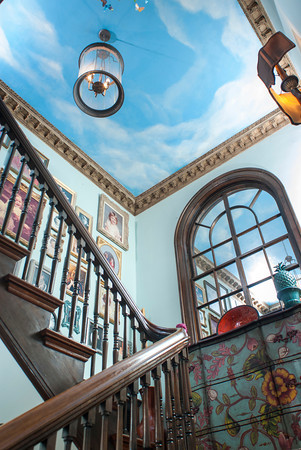 The staircase and landing are painted in a sky blue with a cloudscape on the ceiling.