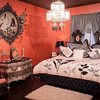 A chandelier hangs in one of the upstairs bedrooms.  The room is decorated in warm colors with silver accents.