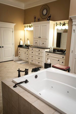 The large whirlpool bathtub is enclosed in a tile pedestal.