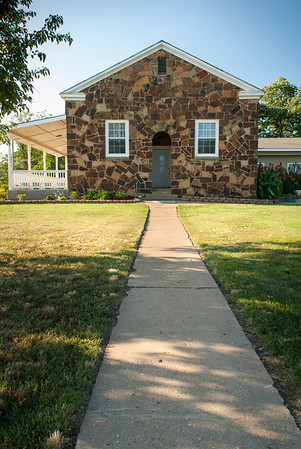 Gary and Jan Jobe have converted a WPA schoolhouse into a comfortable home. Siding and a front porch were added to the exterior to soften the look of the building.