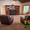 The living room has a high ceiling and large windows overlooking the wooded area surrounding the home.