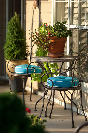 A small café table becomes a display place for a mixed planter of flowers cascading from a terracotta pot on the front porch.