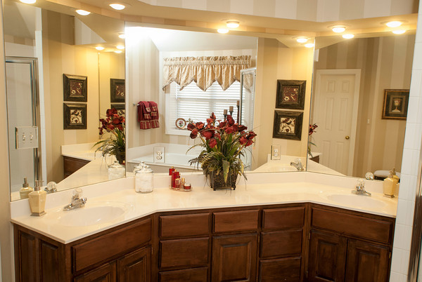 The master bath is reflected in the angled mirrors above the three-part counter.