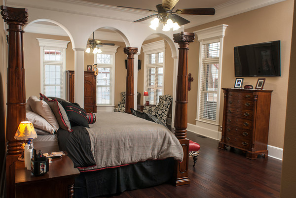 The large sleeping area of the master suite is separated from a seating area by arches and columns.