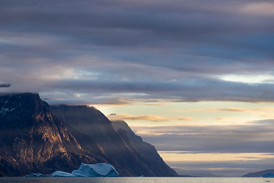 Here the sun is cutting dramatically through a gap in the clouds to light the tall peaks lining the fjord