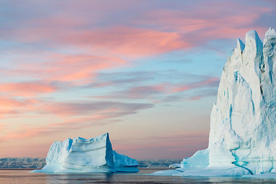 The dramatic light of the Arctic in early fall makes the icebergs of East Greenland look like towering giants floating gracefully across the sea