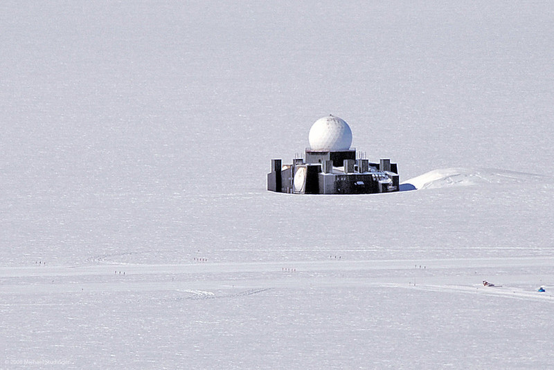 A remnant of the Cold War in the middle of the Greenland ice sheet. This is the radar station DYE-2 that has been part of the Distant Early Warning Line during the Cold War. It has been decommissioned in 1988. Only the upper few stories and the radome are visible. The rest of the building is buried by snow. Today, a skiway and camp nearby are used to train pilots in ski landings.