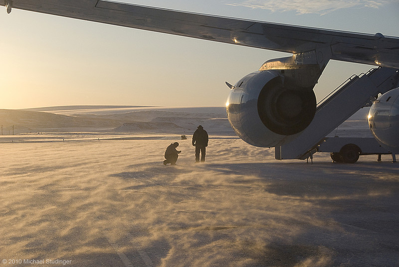 DC-8 crew members Leo Salazar and Scott Silver in blowing snow on the ramp shortly before takeoff from Thule Air Base to the fifth science flight of Operation IceBridge.