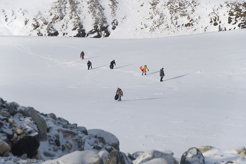 Operation IceBridge team members climb a lateral moraine at the margin of the Greenland Ice Sheet during a no-fly day in Thule.