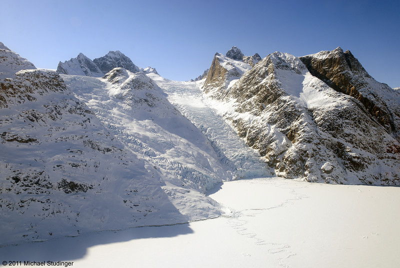 Small glaciers flowing down steep mountain slopes.
