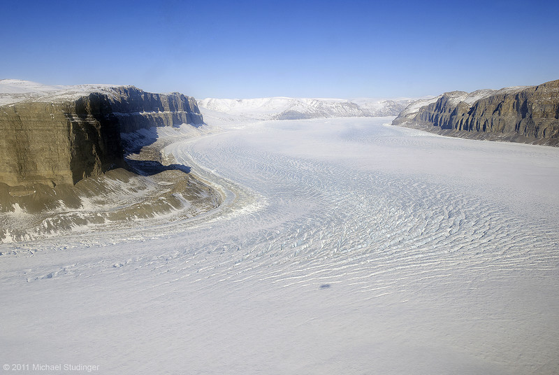 Steensby Glacier in northern Greenland. Steensby Glacier flows around a sharp turn seen here in the image. Note the shadow of the P-3 in the center of the image.