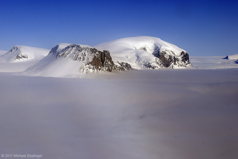 Mountain peaks above Yngvar Nielsen Glacier (covered in clouds) south of Thule.