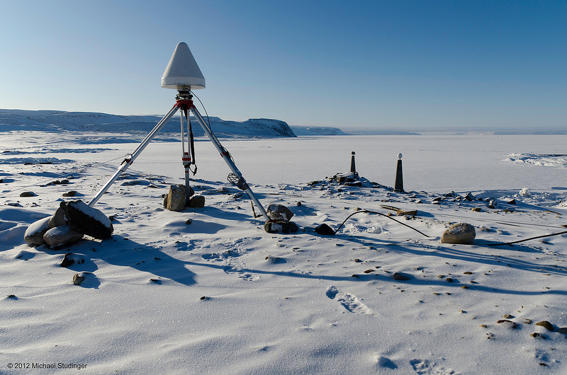 Global Positioning System (GPS) base station at Thule Air Base in Greenland. All aircraft positions are calculated relative to the base station at Thule. The picture shows the choke ring GPS antenna with a protective cone that prevents snow from accumulating on the antenna. The position of this antenna is tied to the two International GNSS Service reference stations right next to it. South Mountain and Wolstenholme Fjord are in the background.