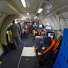 "Inside ""the tube"". Being inside a P-3 Orion with very few windows feels very much like being inside a windowless tube, and therefore the main cabin is affectionately referred to as ""the tube"". Now add the noise and vibrations of four turboprop engines and you will get an idea what it means to be ""not in the office""."