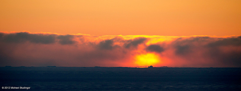 Sunset over the North Star Bay at Thule, Greenland. Thule is located at 76.5°N, 600 nautical miles north of the Arctic Circle and only 800 nautical miles south of the North Pole. The sun behind the cloud bank provides a dramatic illumination for the icebergs and the sea ice in the North Star Bay on this chilly and breezy evening with temperatures of -45°C/-50°F with windchill.