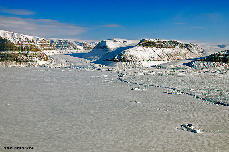 The new calving front of Petermann Glacier. In July 2012 an iceberg twice the size of Manhattan has broken off Petermann Glacier. As a result of this calving event the new calving front is several kilometers upstream now. Several valley glaciers are now flowing into the fjord, covered by sea ice.