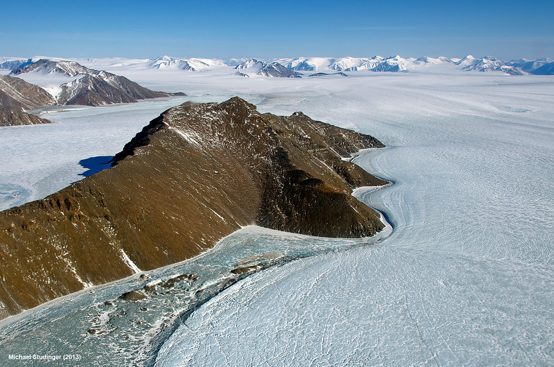 Ice is a plastic material the slowly deforms under its own weight.The ice flows around mountains that are in its way. Here you can see an example from northeast Greenland, where the glacier is hugging a ridge, nicely flowing around it.