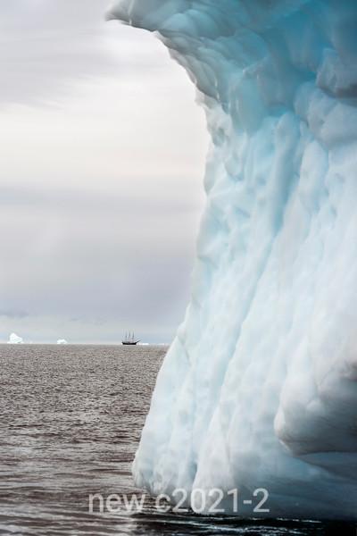 Curving iceberg with distant Rembrandt van Rijn schooner, Schoresby Sund, East Greenland