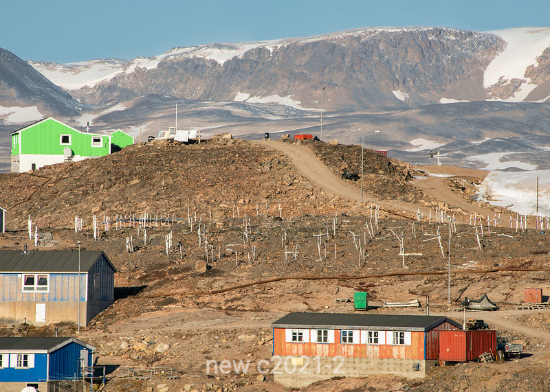 Old graveyard with snow patches and mountains in Ittoqqortoormiit, Lincoln Land, Scoresby Sund, Greenland
