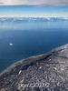 Flying over Jameson land towards Scoresby Sund with icebergs and the Volquaart von Kyst coast, East Greenland