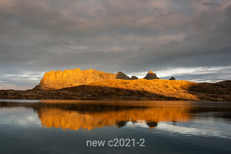 Bjorn Islands catching the setting sun and reflected in Halll Bredning, Scoresby Sund, Greenland