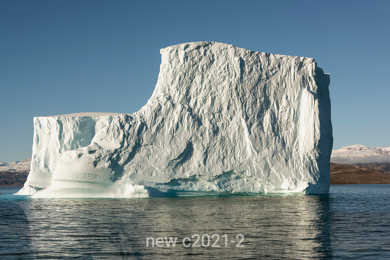 Steep flat-topped iceberg reflected in the water near Jameson Land in Hall Bredning, Scoresby Sund, Greenland
