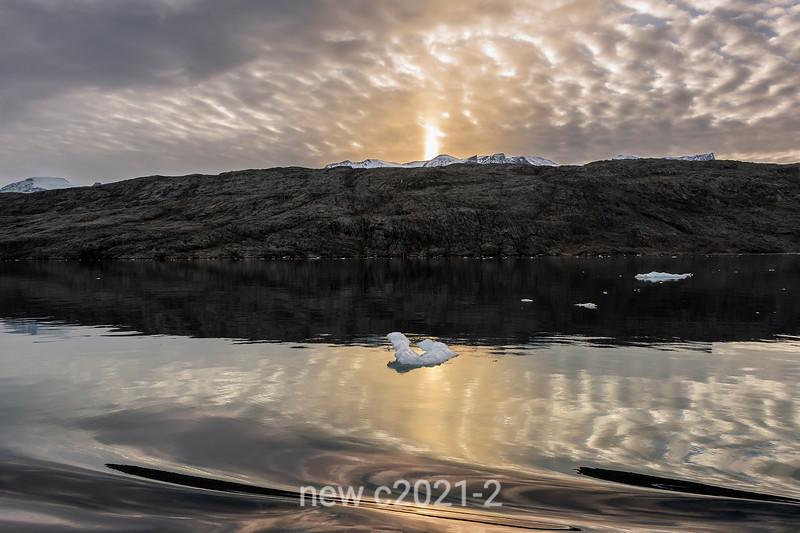 Reflections, sun pillar and growler at sunset, Bjorn Islands, Hall Bredning, Scoresby Sund, Greenland