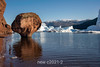 Rode O red beach with rock mushroon and icebergs with MIlne Land in BG, Scoresby Sund, Greenland
