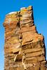Columnar basalt column with red and orange lichen and grasses, Rode O, Rodefjord, Scoiresby Sund, Greenland
