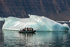Photographers close up to a small blue iceberg, Vikingebugt Inlet, Scorseby Sund, Greenland