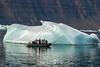 Photographers close up to a small blue iceberg, Vikingebugt Inlet, Scorseby Sund, Greenland