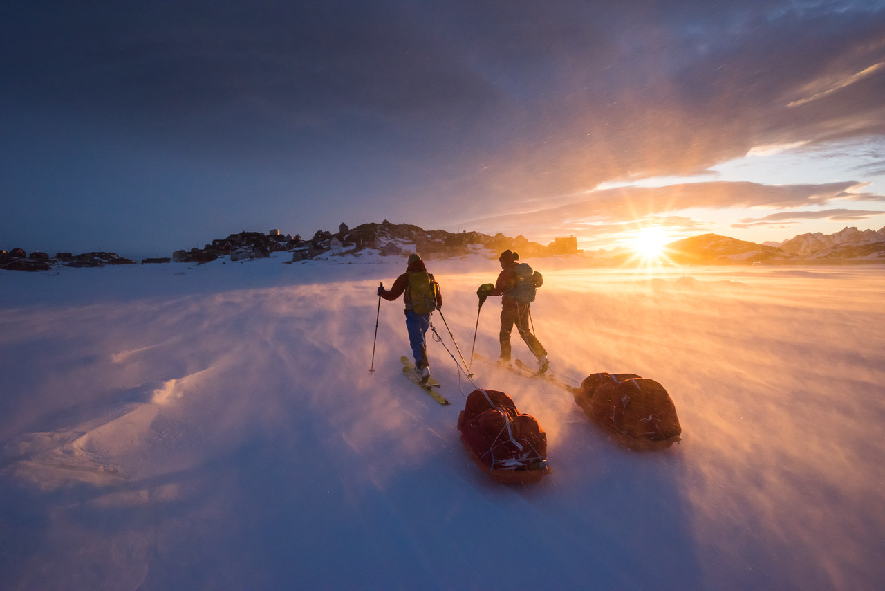 Dragging pulks back over the sea ice to Kulusuk at sunset, East Greenland