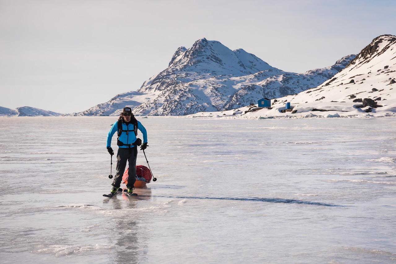 Adam Craig skating away from a hunter's cabin, East Greenland