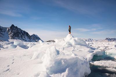 Inuit boat driver searching for a passage through dense bergy bits, Ammassalik Fjord