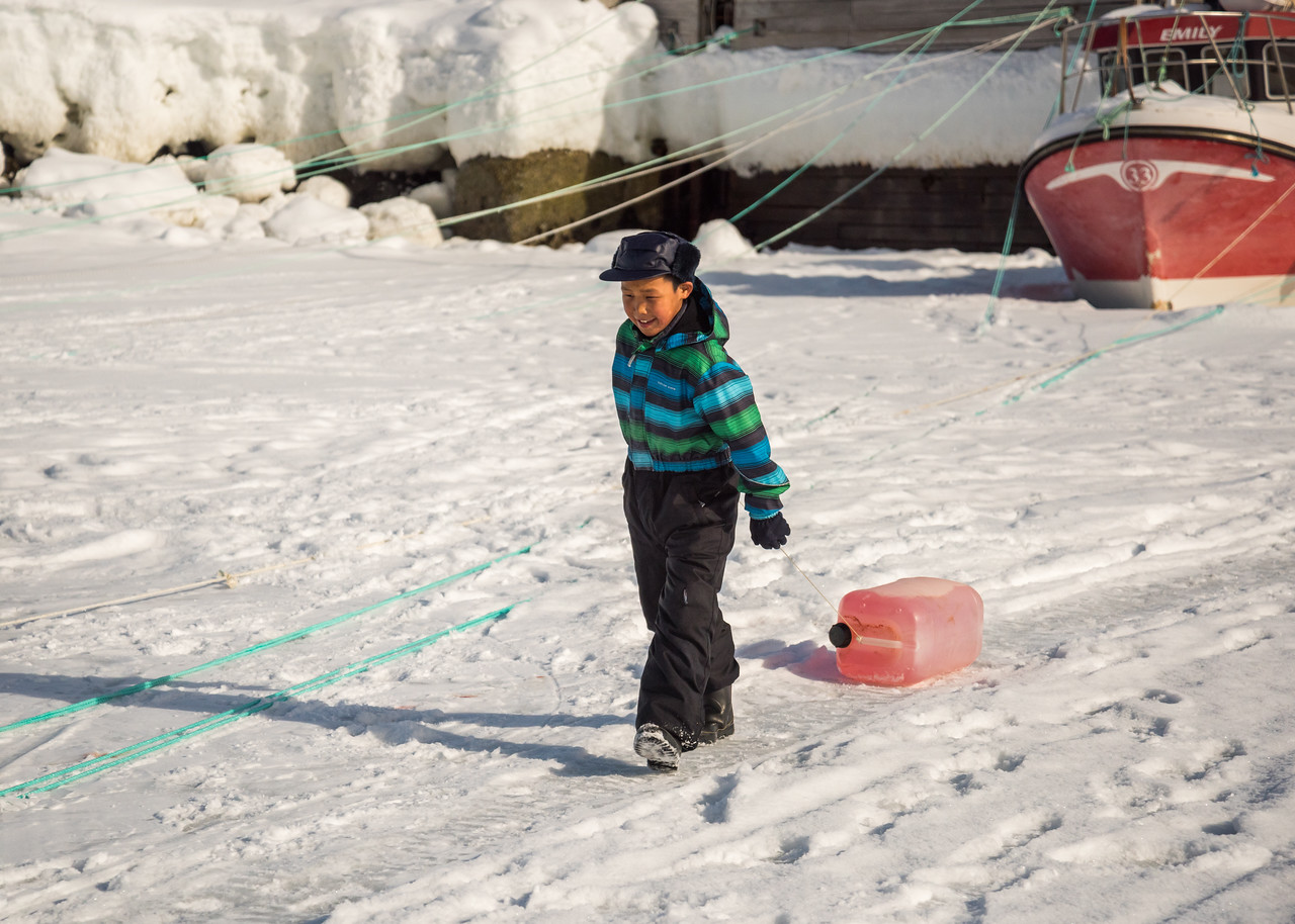 Inuit boy dragging diesel towards the boats, Kuummiit