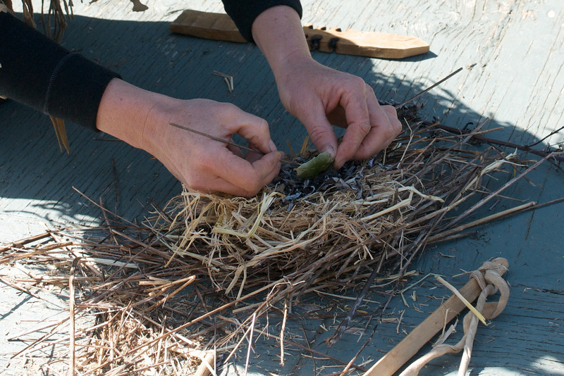 The coal is gently pushed onto a nest of dried mugwort that sits on very flammable kindling.
