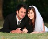 Beautiful wedding couple laying down outdoors on the grass, Beautiful wedding couple laying down outdoors on the grass