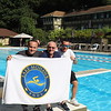 Myself, My Father, and Teddy (formerly mentioned twin) Holding up a towel with the logo of the pool while sitting on one of the diving boards