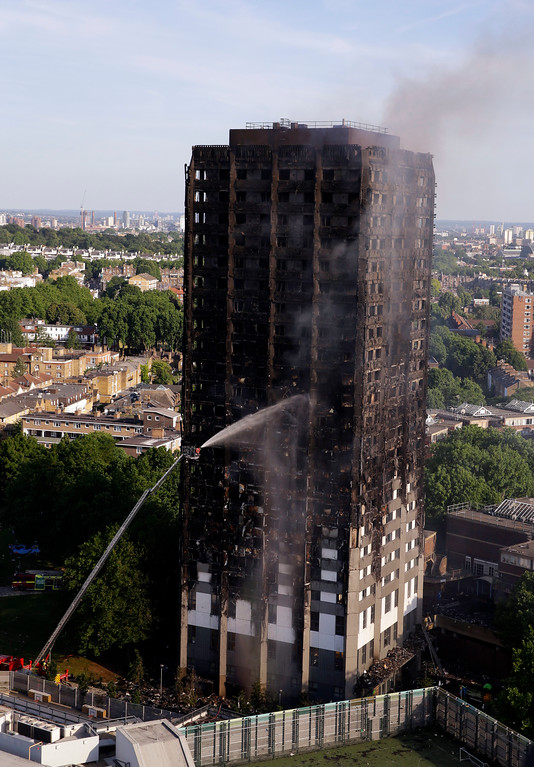 . Firefighters work at the scene after a deadly blaze at a high rise apartment block in London, Wednesday, June 14, 2017. Fire swept through a high-rise apartment building in west London early Wednesday, killing an unknown number of people with around 50 people being taken to hospital. (AP Photo/Alastair Grant)