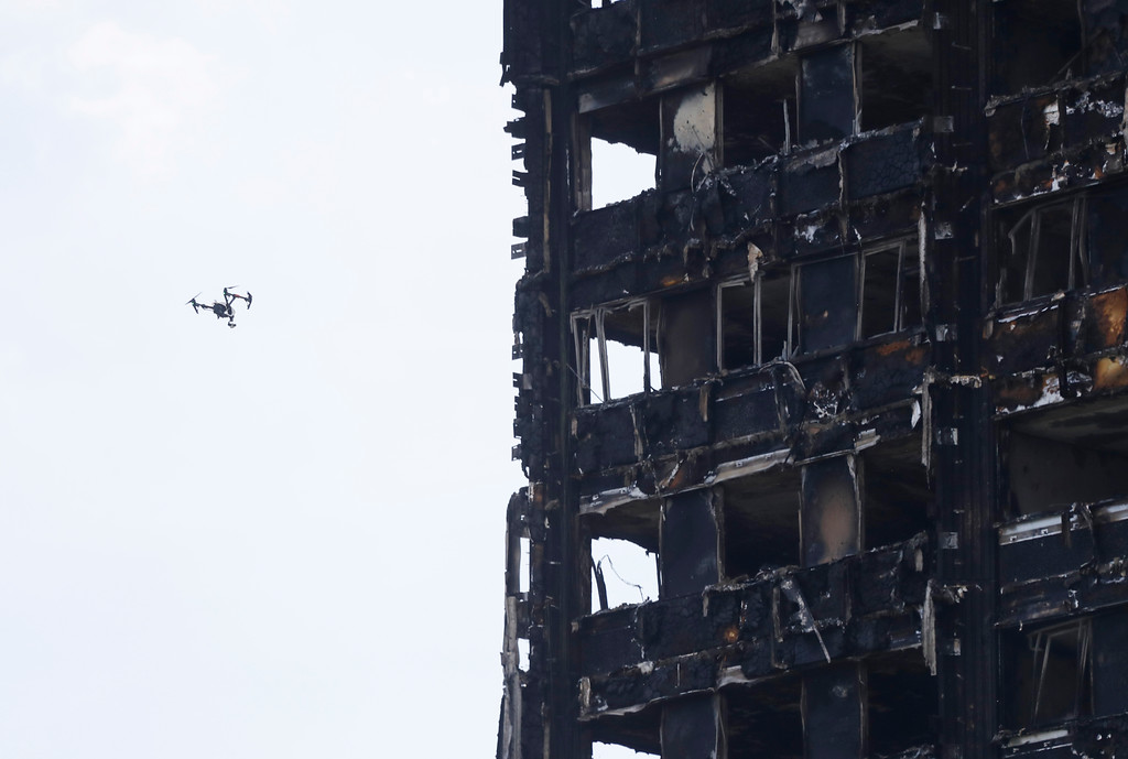 . A drone flies past the high-rise apartment building where a massive fire raged, in London, Wednesday, June 14, 2017. A deadly overnight fire raced through a 24-story apartment tower in London on Wednesday, killing at least six people and injuring more than 70 others. (AP Photo/Frank Augstein)
