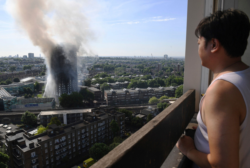 . A woman watches as smoke billows from a fire that has engulfed the 24-storey Grenfell Tower in west London, Wednesday June 14, 2017. Fire swept through a high-rise apartment building in west London early Wednesday, killing an unknown number of people with around 50 people being taken to hospital. (Victoria Jones/PA via AP)