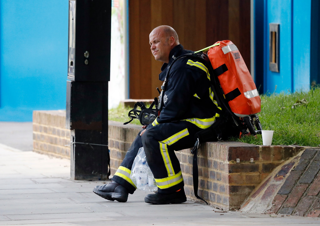 . A fire officer rests near the high-rise apartment building where a massive fire raged overnight, in London, Wednesday, June 14, 2017. A deadly overnight fire raced through a 24-story apartment tower in London on Wednesday, killing at least six people and injuring more than 70 others. (AP Photo/Frank Augstein)