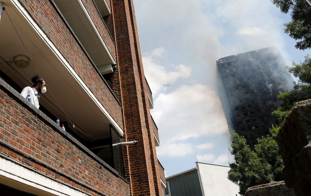 . A man wearing a mask for protection from the smoke, stands on a balcony and looks at the high-rise apartment building where a massive fire raged, in London, Wednesday, June 14, 2017. A deadly overnight fire raced through a 24-story apartment tower in London on Wednesday, killing at least six people and injuring more than 70 others. (AP Photo/Frank Augstein)