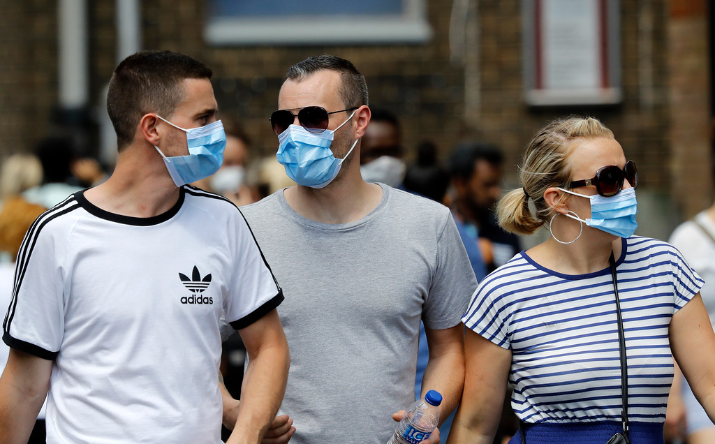 . People wear masks as protection from the smoke near the high-rise apartment building where a massive fire raged overnight, in London, Wednesday, June 14, 2017. A deadly overnight fire raced through a 24-story apartment tower in London on Wednesday, killing at least six people and injuring more than 70 others. (AP Photo/Frank Augstein)