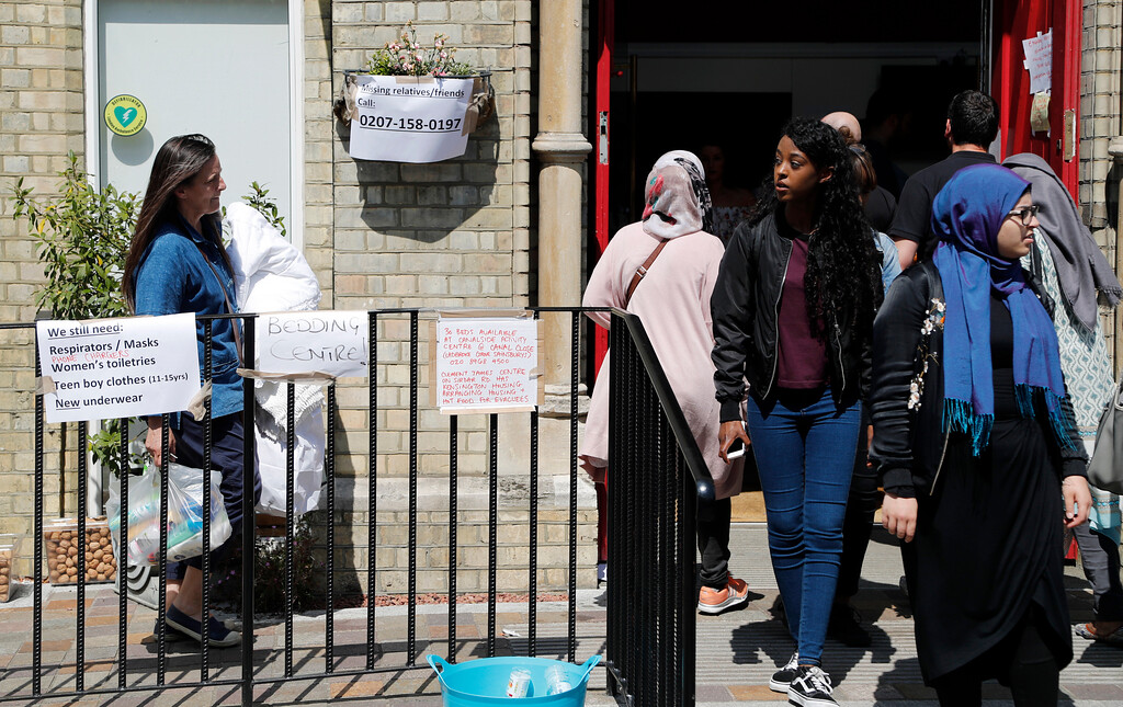 . People enter and exit the center offering emergency supplies near the high-rise apartment building where a massive fire raged overnight, in London, Wednesday, June 14, 2017. A deadly overnight fire raced through a 24-story apartment tower in London on Wednesday, killing at least six people and injuring more than 70 others. (AP Photo/Frank Augstein)