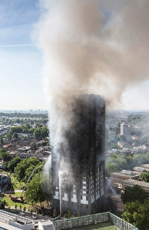 . Smoke billows after a fire engulfed the 24-storey Grenfell Tower, in west London, Wednesday June 14, 2017. Fire swept through a high-rise apartment building in west London early Wednesday, killing an unknown number of people with around 50 people being taken to hospital. (Rick Findler/PA via AP)