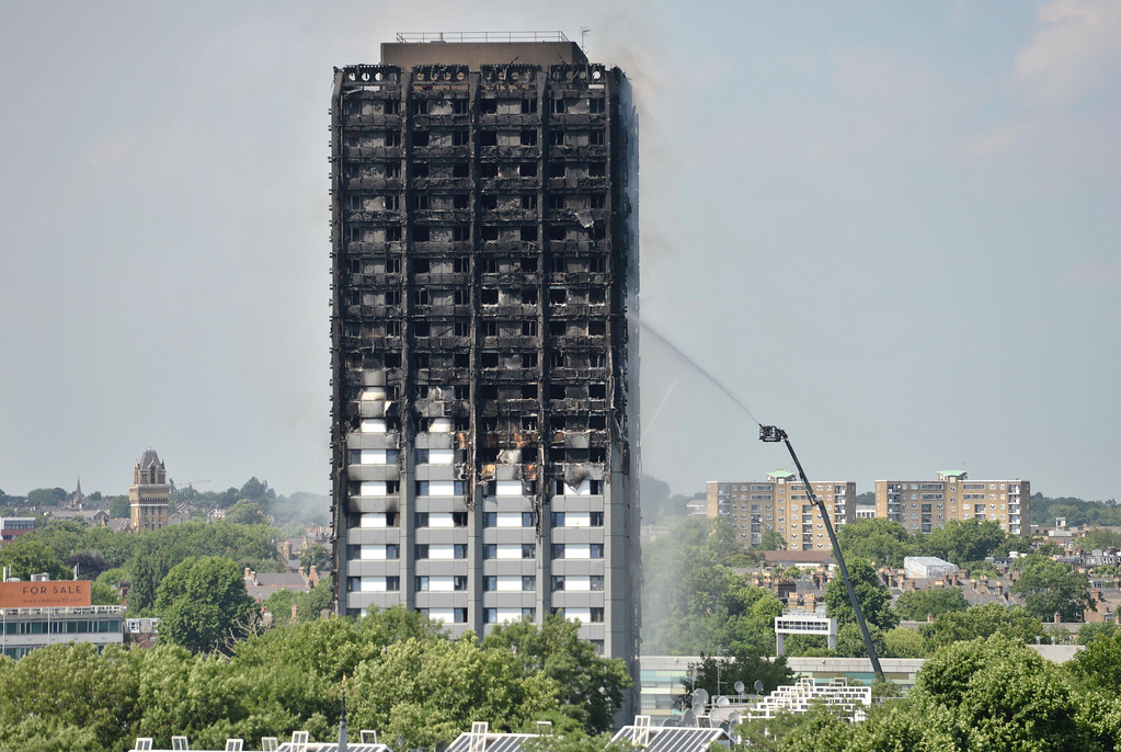 . Firefighters spray water onto the 24-storey apartment block in west London. Wednesday June 14, 2017.  Firefighters are searching the charred 24-storey apartment tower in London after a deadly overnight fire raced through it. Police say there were fatalities with more than 70 othersinjured in the blaze that sent black smoke over the British capital. (Victoria Jones/PA via AP)