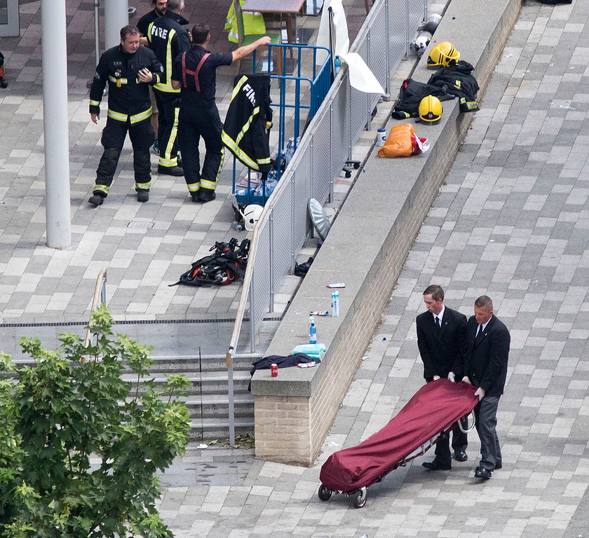 . Bodies are removed from the scene after a fire engulfed the 24-storey Grenfell Tower, in west London, Wednesday June 14, 2017. Fire swept through a high-rise apartment building in west London early Wednesday, killing an unknown number of people with around 50 people being taken to hospital. (Rick Findler/PA via AP)
