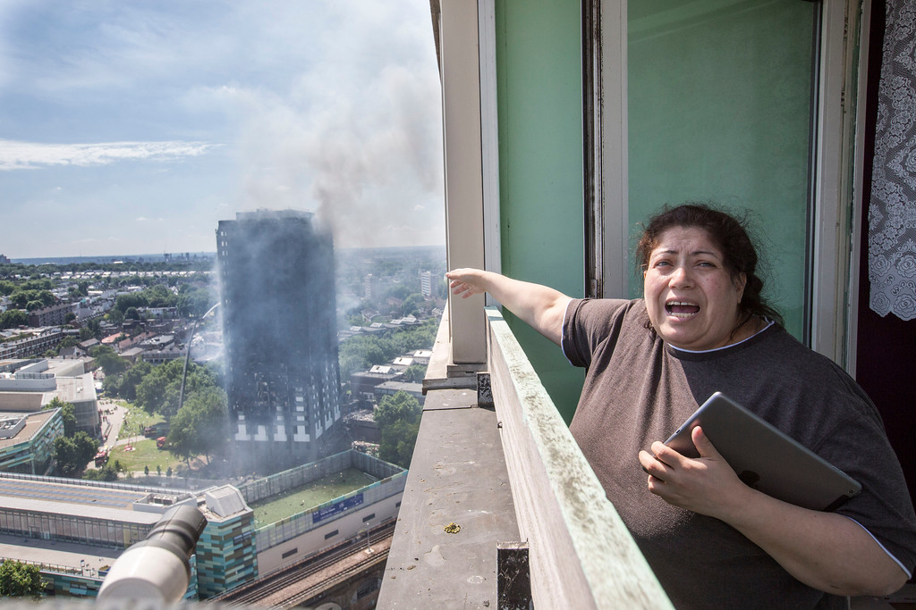 . Local resident Georgina stands distraught on her balcony after a fire engulfed the 24-storey Grenfell Tower, in west London, Wednesday June 14, 2017. Fire swept through a high-rise apartment building in west London early Wednesday, killing an unknown number of people with around 50 people being taken to hospital. (Rick Findler/PA via AP)